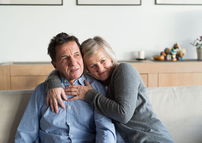 senior woman and man sitting on a couch