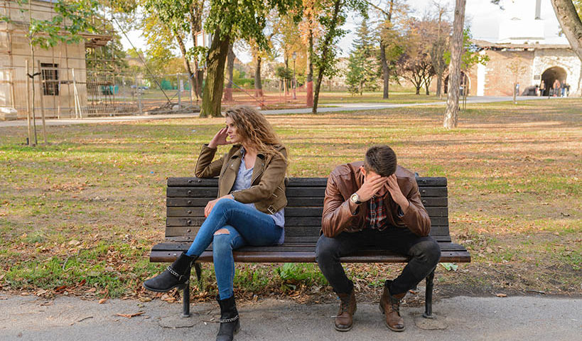 upset couple on park bench