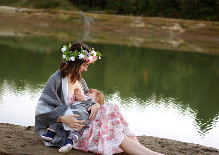 young woman breastfeeding on riverside