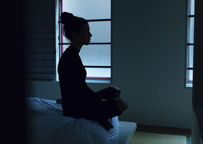 young woman meditating on bed